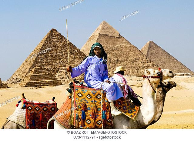 An Egyptian man and his camel asking tourist to come for a ride around the great Pyramids of Giza, Egypt