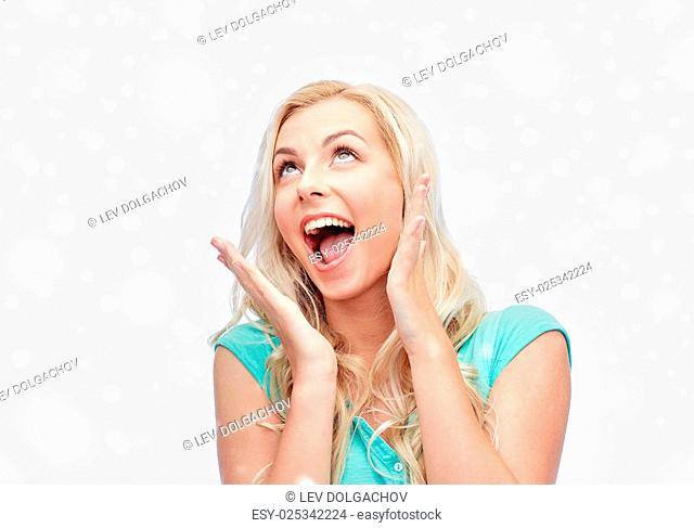 emotions, expressions, winter holidays, christmas and people concept - surprised smiling young woman or teenage girl over snow