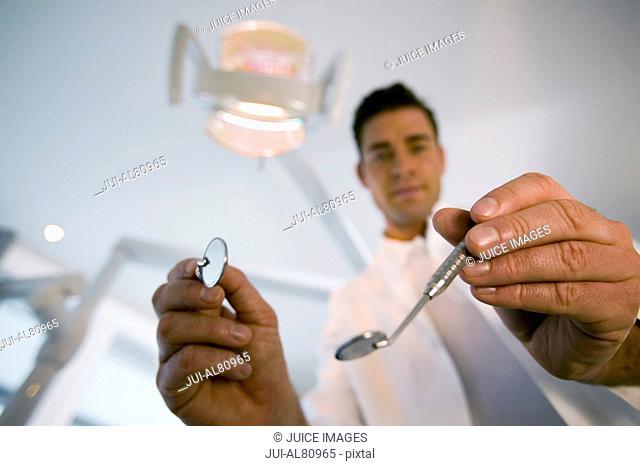 Male dentist holding dental mirrors