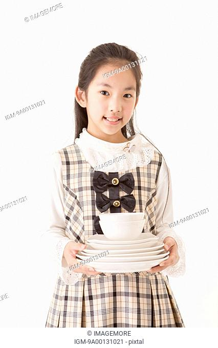 Girl holding a set of plates and bowls