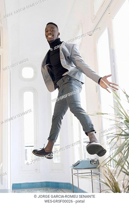 Portrait of smiling young businessman jumping in the air in his office