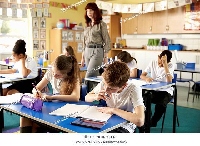 Teacher walking in her busy primary school classroom