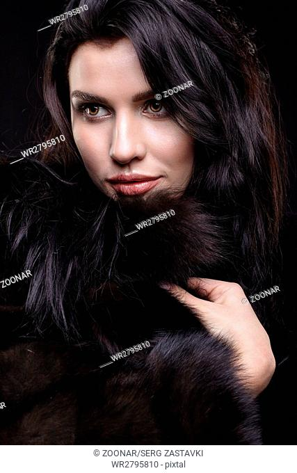 Portrait of a young brunette woman with long black hair dressed in a fur coat