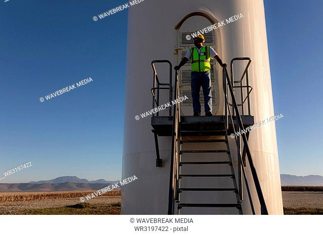 Engineer standing at entrance of a wind mill