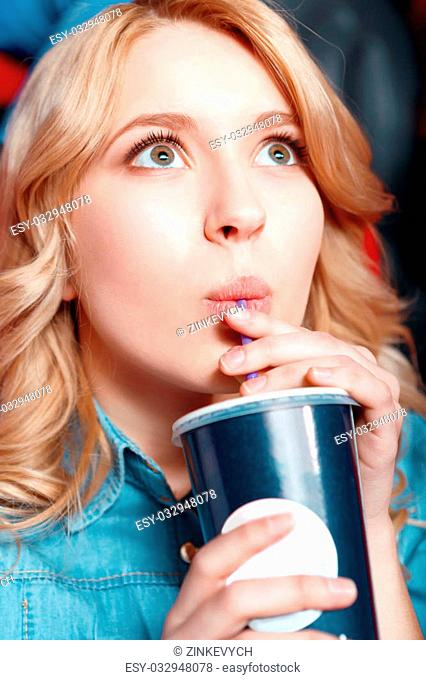 Rapturous girl. Young blond woman enthusiastically watching film and drinking coke in cinema