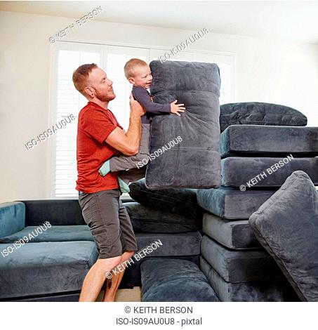 Father and son stacking cushions in living room