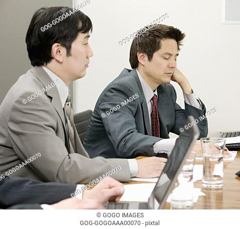 Three businessmen in board meeting, close-up
