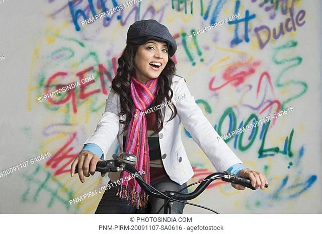 Portrait of a woman riding a bicycle in front of a graffiti covered wall