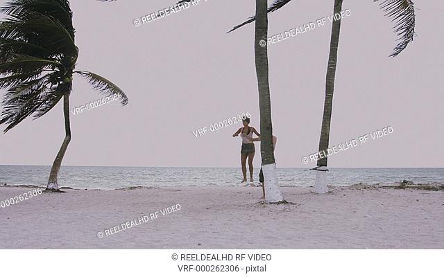 Young man teaching slacklining to teenage girl at beach
