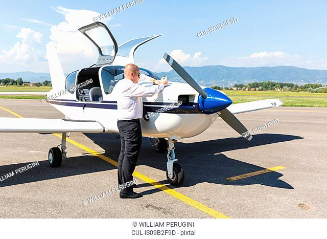 Pilot standing by small aircraft