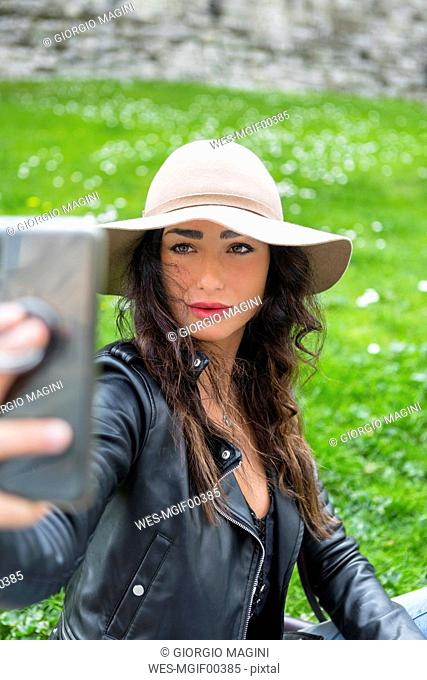 Young woman with hat taking a selfie