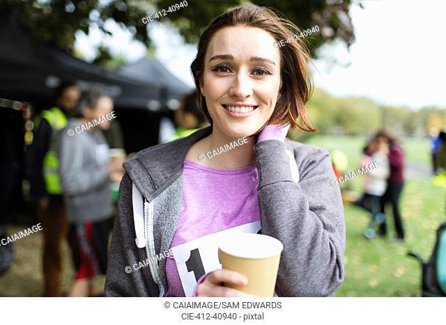 Portrait smiling female marathon runner drinking water in park