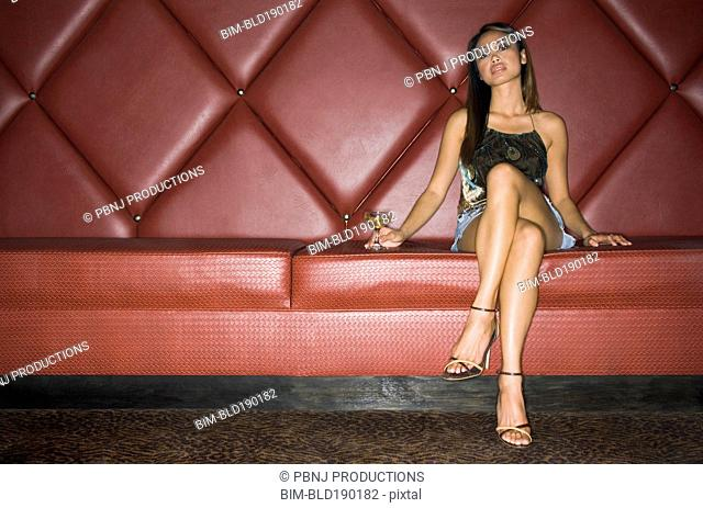 Asian woman with cocktail in cushioned booth