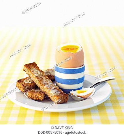 Boiled egg in striped egg cup with toast and spoon on white plate on checked tablecloth, close-up