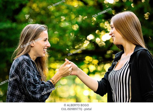 Two young female friends giving secret handshake in park