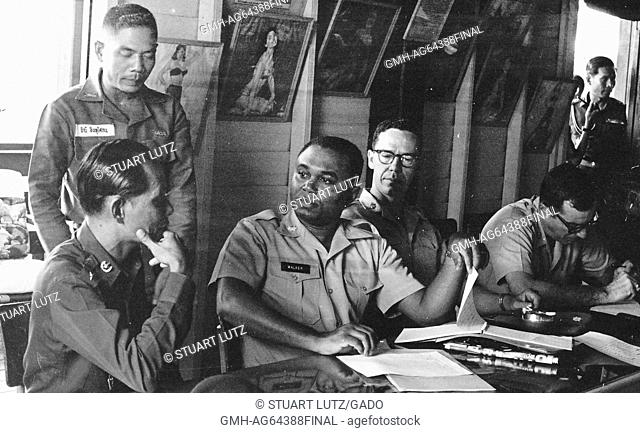 Lieutenant AL Walker sitting at a long table, indoors, with two American soldiers, talking to two Vietnamese soldiers, one sitting, one standing, Vietnam, 1964