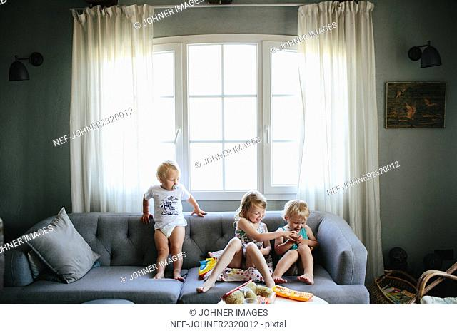 Kids on sofa using tablet