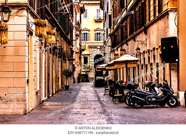 Scooters and a street cafe in a typical narrow Rome street