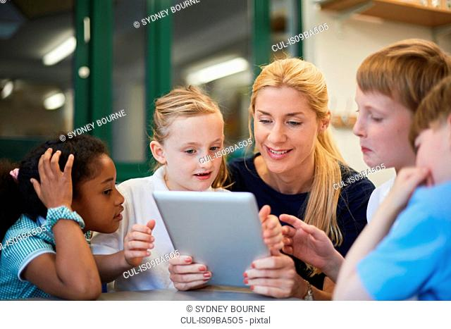 Teacher with schoolboys and girls looking at digital tablet in classroom at primary school
