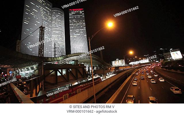 Exterior, LS, Locked Down Shot, Nighttime, View of the Ayalon Traffic Lanes, among the busiest roads in Israel. Seen are the triple Azrieli Towers, the circular