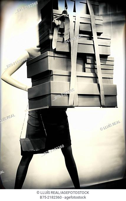 Mannequin of a window of a fashion store holding in his hands a lot of boxes tied with a ribbon in London, England, UK