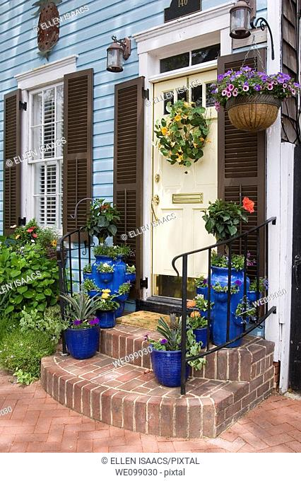 Door of an attractive colonial style house with flowers in blue flower pots on the brick steps, in a hanging planters, and on a wreath on the door  Annapolis