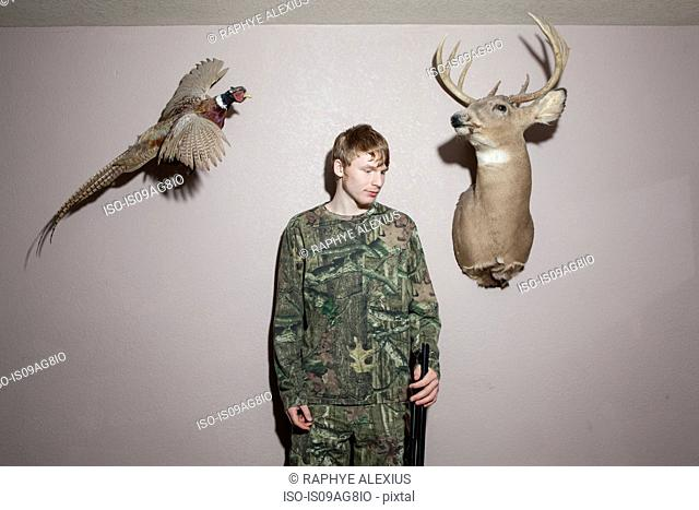 Home portrait of teenage boy holding shotgun