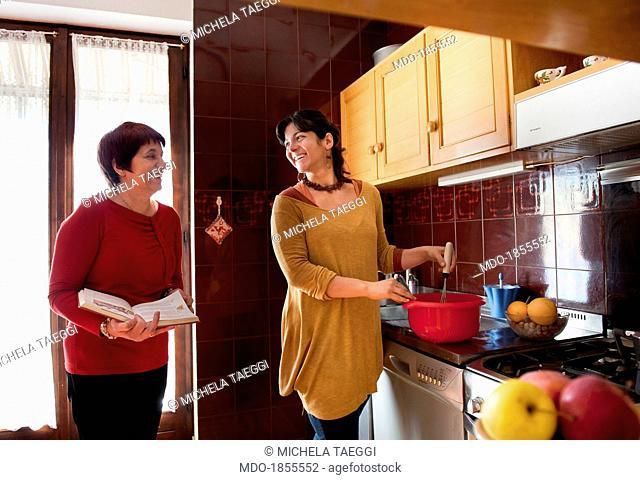 Two smiling women in home kitchen. Cohousing. Trento (Italy), November 2013