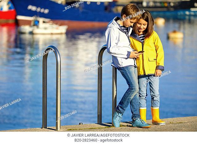 Children with raincoat, Port of Getaria, Gipuzkoa, Basque Country, Spain, Europe