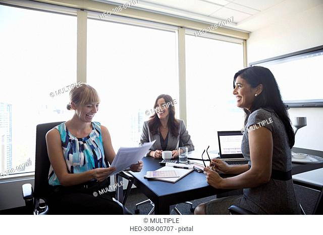 Smiling businesswomen reviewing paperwork in conference room meeting