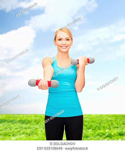 sport, excercising and healthcare concept - young sporty woman with light dumbbells