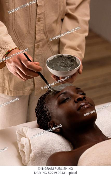 Professional beautician applying mud mask to african woman at spa salon