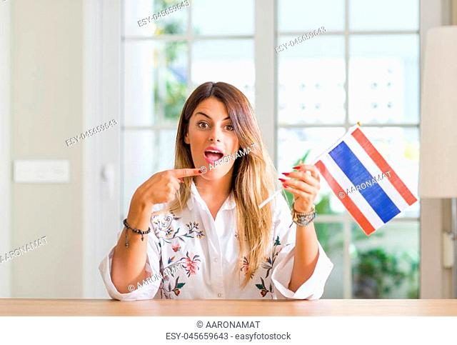 Young woman at home holding flag of Thailand very happy pointing with hand and finger