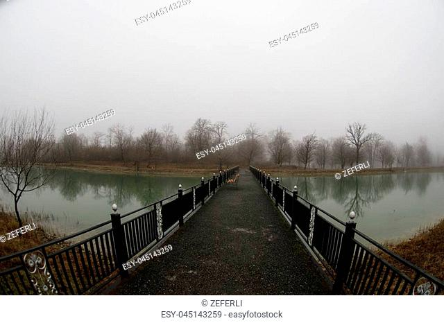 Amazing landscape of bridge reflect on surface water of lake, fog evaporate from pond make romantic scene or Beautiful bridge on lake with trees at fog