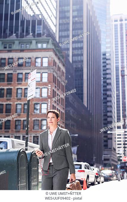 USA, New York City, businesswoman in Manhattan with with cell phone and earphones
