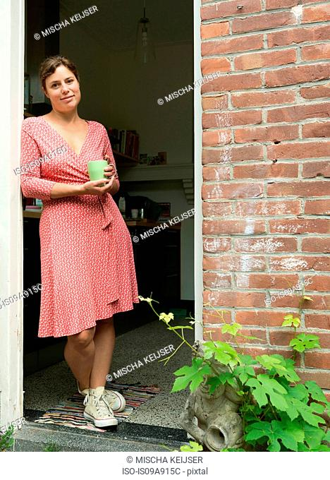Woman standing in doorway holding mug