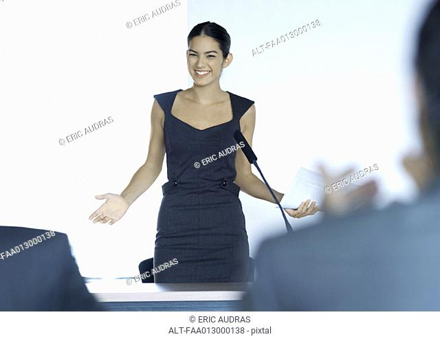 Businesswoman speaking with microphone during seminar