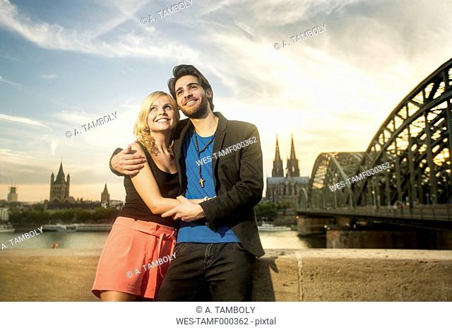 Germany, Cologne, happy young couple standing in front of Rhine River