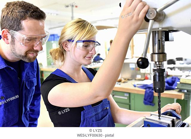 Instructor with female trainee at drill machine