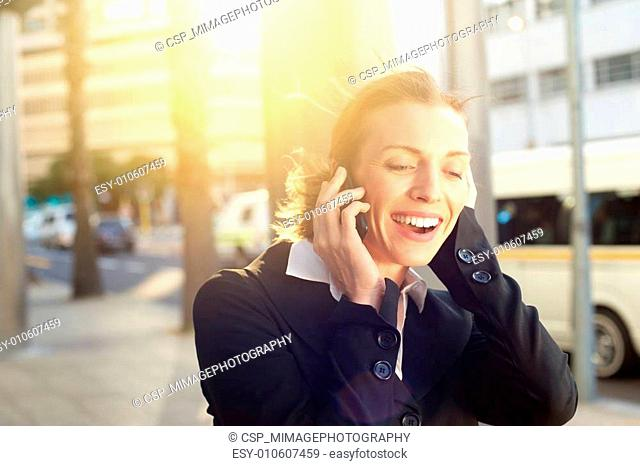 Beautiful business woman smiling on mobile phone outdoors