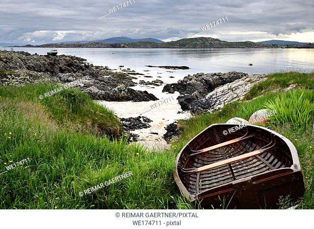 Rocky shore of Isle of Iona with beached boat with Fionnphort Isle of Mull and mountains of Ben More past Sound of Iona Inner Hebrides Scotland UK