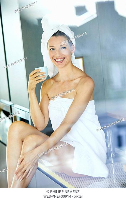 Portrait of smiling woman wrapped in towels drinking cup of coffee in the kitchen