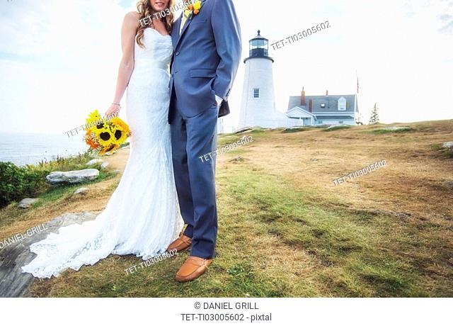 Low section of married couple, lighthouse in background