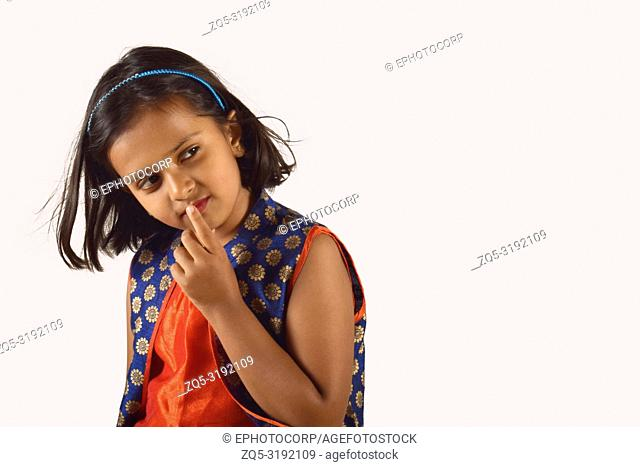 Little girl posing in front of camera with finger on lip in thinking pose. Pune, Maharashtra