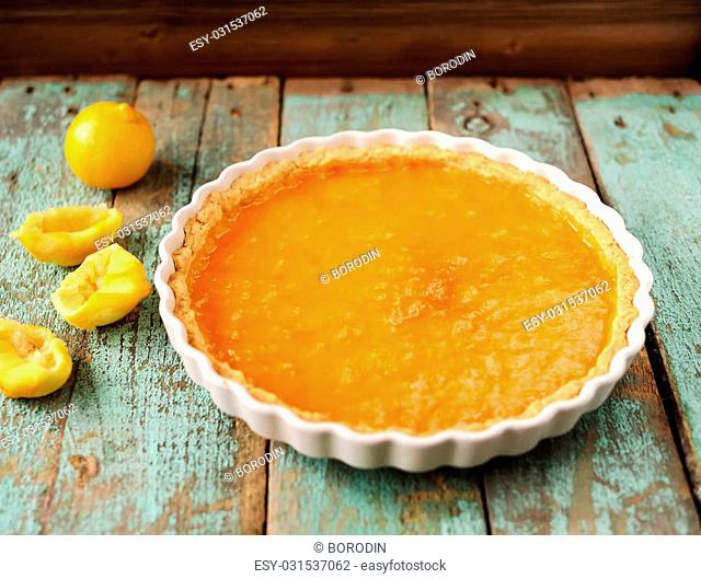 Lemon tart with fresh lemons closeup