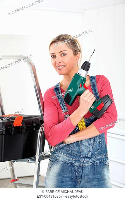 Beautiful blond woman holding electric drill