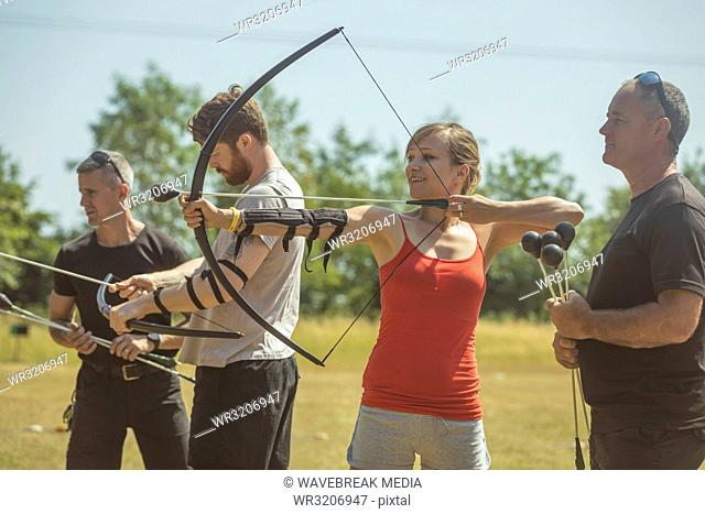 Trainer instructing woman about archery