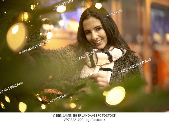 portrait of playful young woman behind lights of Christmas tree, wearing fashionable winter clothes and scarf, in city Munich, Germany