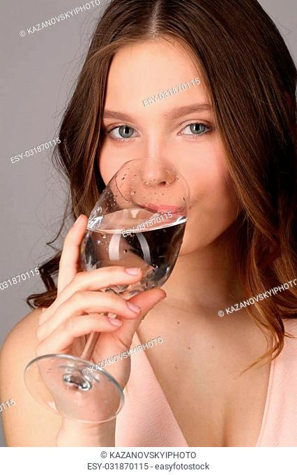 Girl drinking water from a bocal, high fashion look, healthy lifestyle, beautiful girl, smiling girl, isolated, perfect make-up, big lips, model in studio