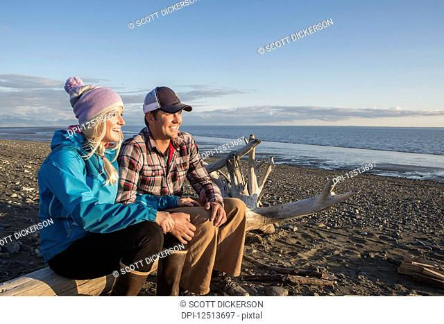 A young couple sits on a piece of driftwood on a beach looking out to the ocean at sunset; Anchorage, Alaska, United States of America